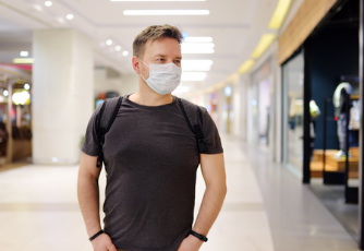 man in a hallway with a mask on his face